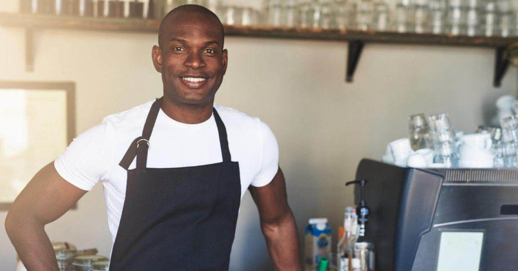 Ein Mann trägt ein weißes Shirt und eine schwarze Schürze und steht in der Küche neben einem Kaffeevollautomaten
